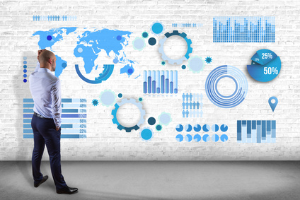 Businessman in front of a wall thinking about a business graph and chart interface - business concept
